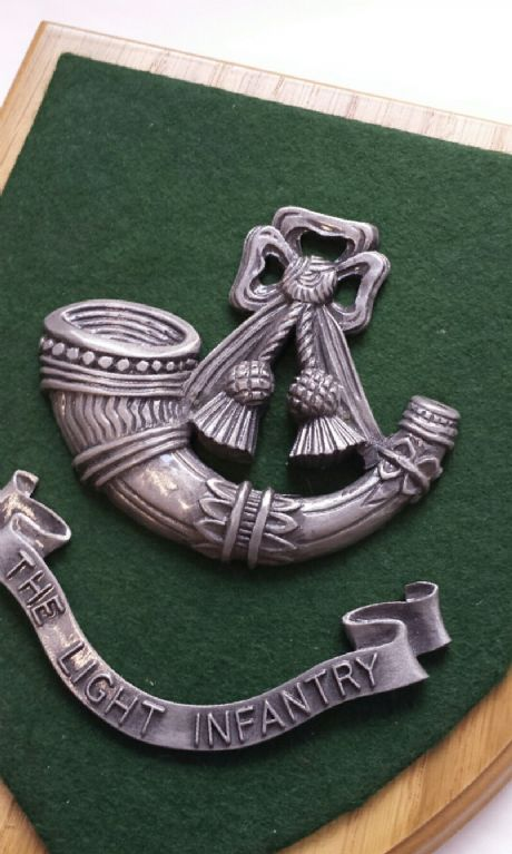 Metallic finished Light Infantry bugle cap badge set against dark green cloth on a solid wooden plaque. The Light Infantry wall plaque.